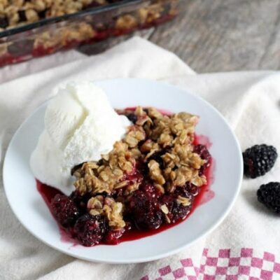 serving of blackberry crisp on a white plate with vanilla ice cream. Set on top of a white and red/white checked cloth napkin. Pan of crisp in the background + fresh blackberries