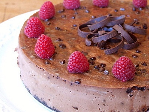 Chocolate Chocolate Chip Cheesecake garnished with raspberries