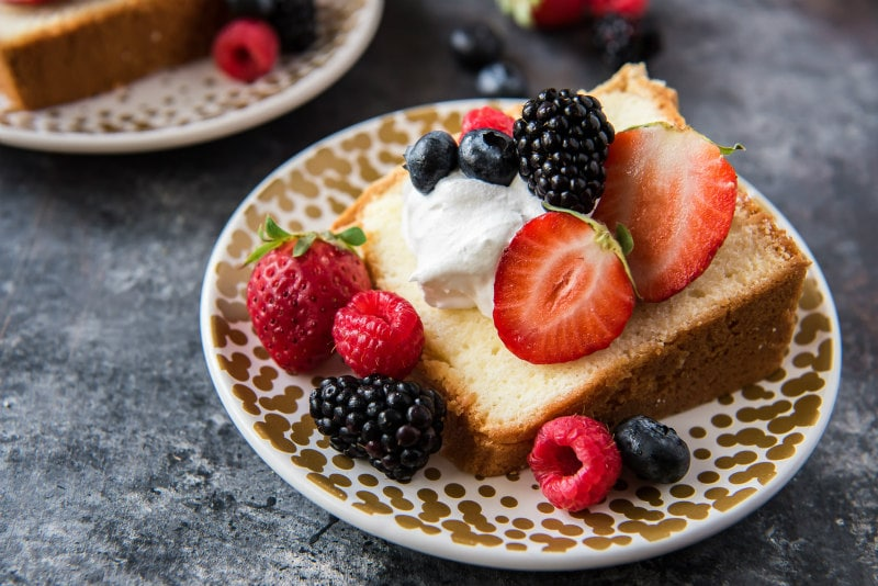 Slice of Cream Cheese Pound Cake with whipped cream and fresh berries