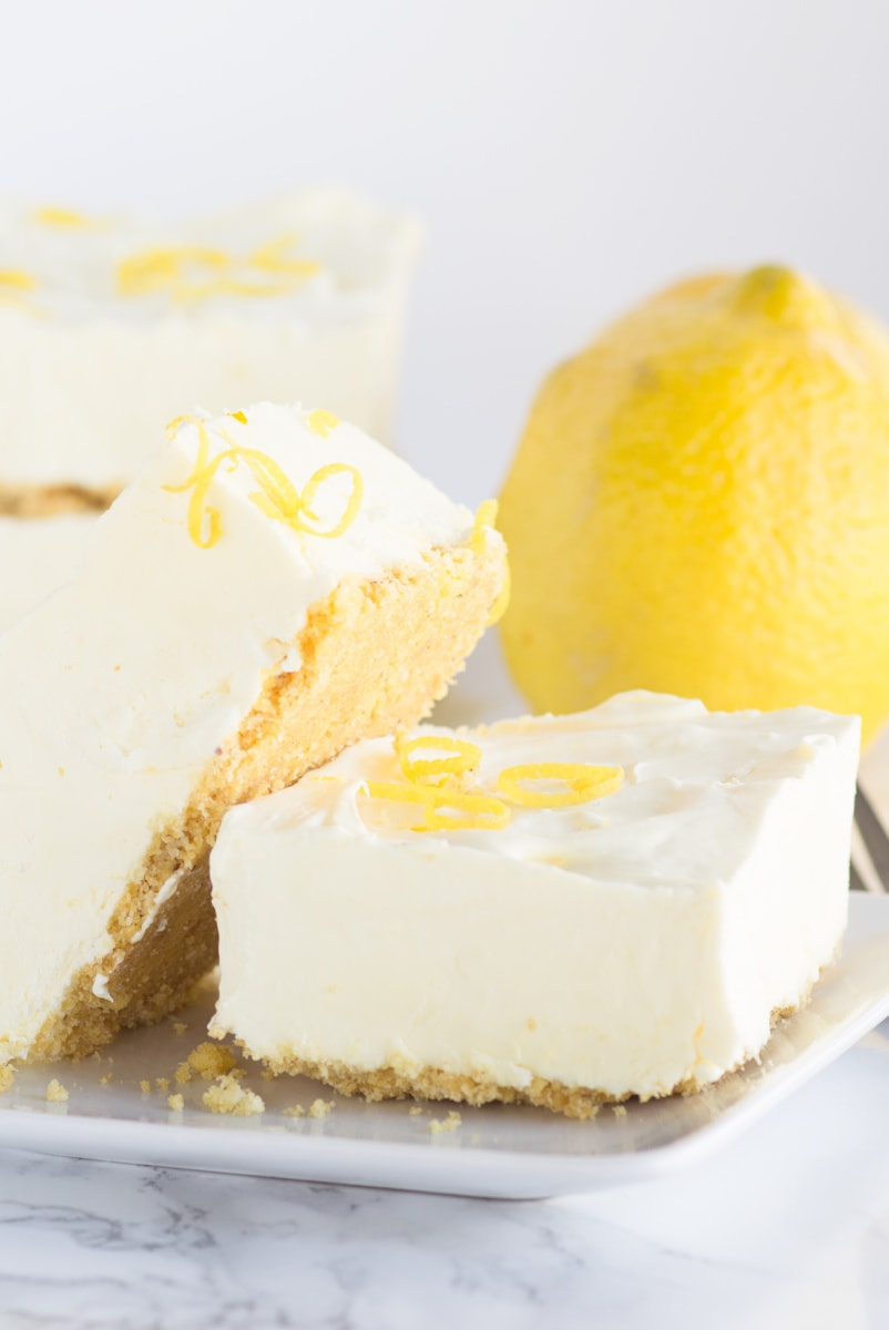 frozen lemon cheesecake squares displayed on white plate with a lemon