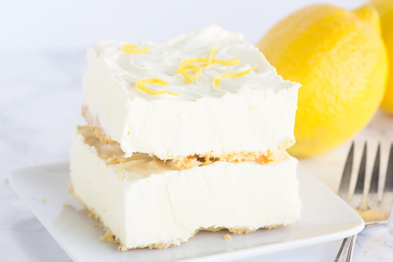 two frozen lemon cheesecake squares stacked on a white plate