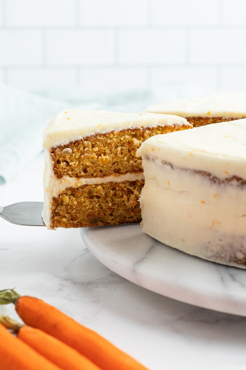 slice being taken out of gingered carrot cake
