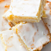 lemon bars stacked haphazardly on a white plate
