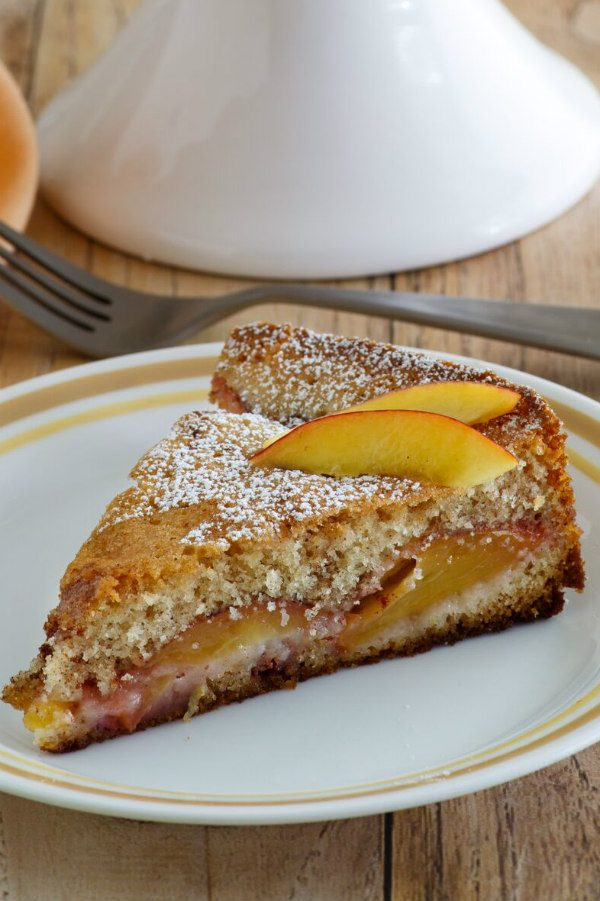 Slice of Nectarine Coffee Cake on a white plate with a yellow stripe around the edge. Fork behind the plate
