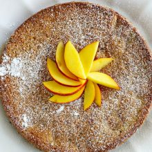 overhead shot of nectarine coffee cake displayed on a white plate with sliced nectarine on top