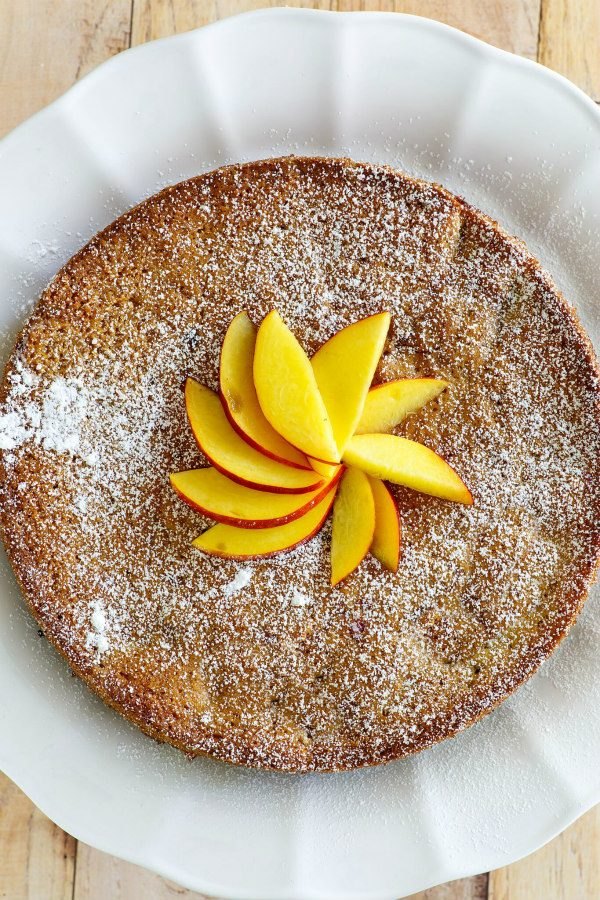 Overhead shot of nectarine coffee cake with fresh nectarines decoratively on top displayed on a white platter