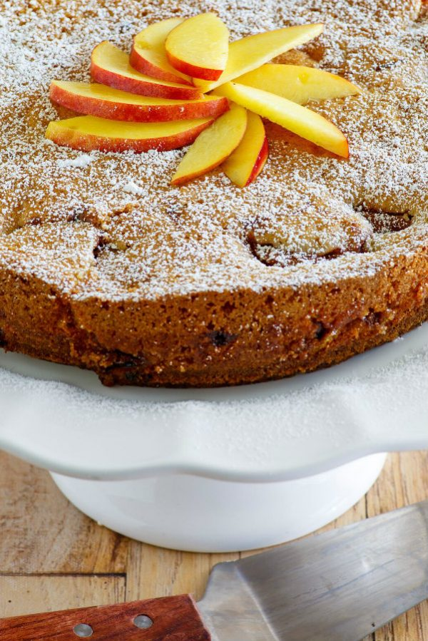 Nectarine Coffee Cake displayed on a white serving platter with fresh nectarines on top. serving spatula alongside.