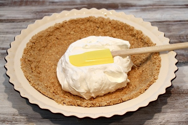 Graham Cracker Crust in pie plate with cream cheese layer spreading on top