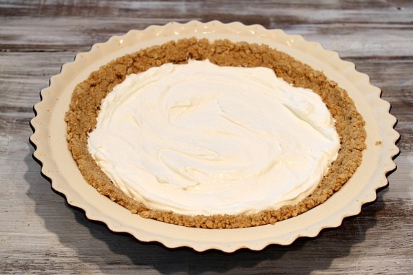 Graham cracker crust in pie plate with cream cheese layer on top