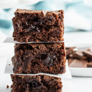 3 stacked brownies with chopped chocolate in the forefront