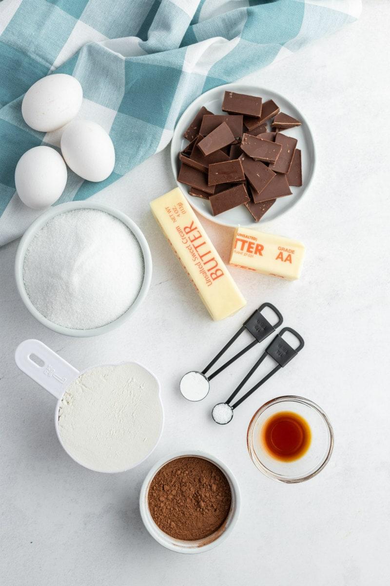 overhead shot of ingredients displayed for ooey gooey brownies- eggs, sugar, flour, cocoa, vanilla, butter, chocolate