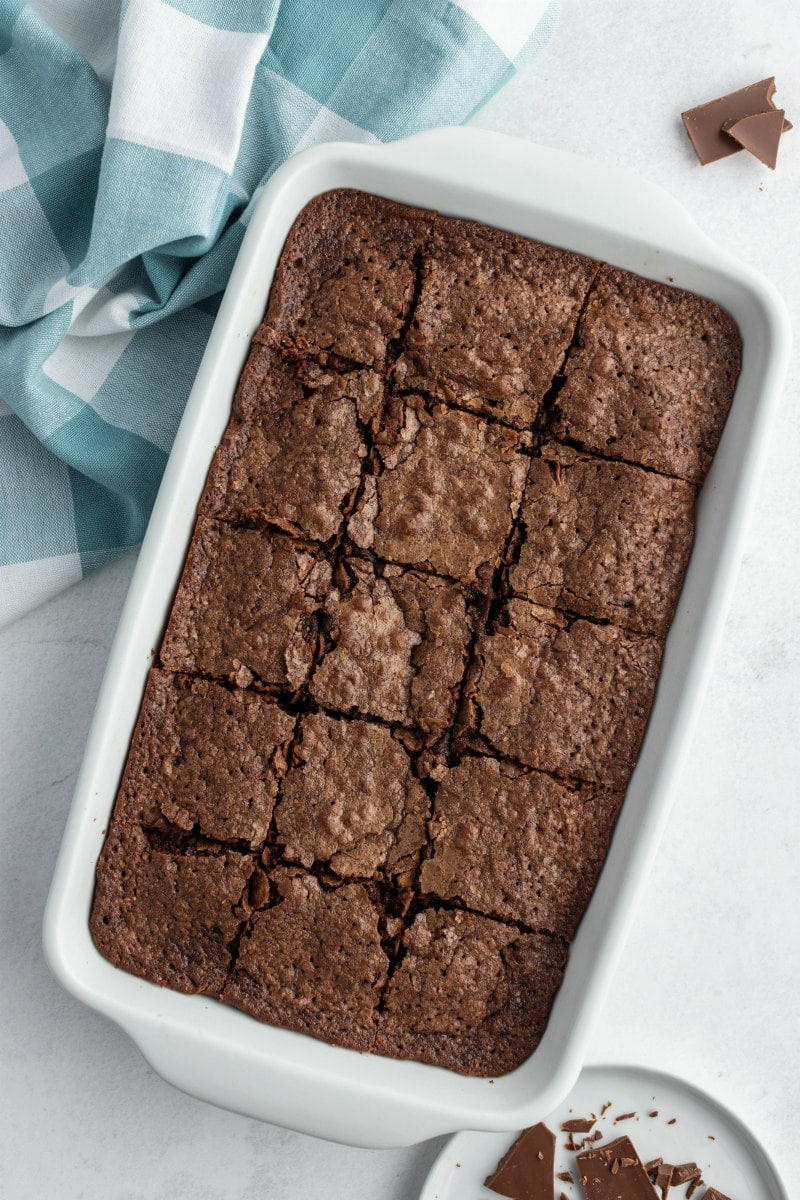 pan of sliced brownies with a blue/white checked napkin in the background