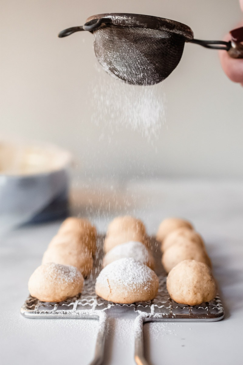 sprinkling powdered sugar on hot pecan sandies