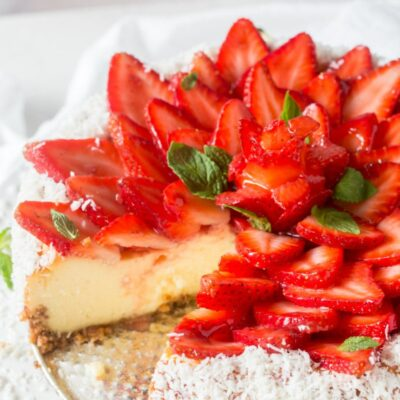 strawberry coconut cheesecake on platter with a slice removed
