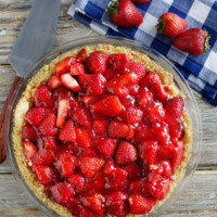 overhead shot of strawberry pie with blue/white checked napkin and fresh strawberries in background