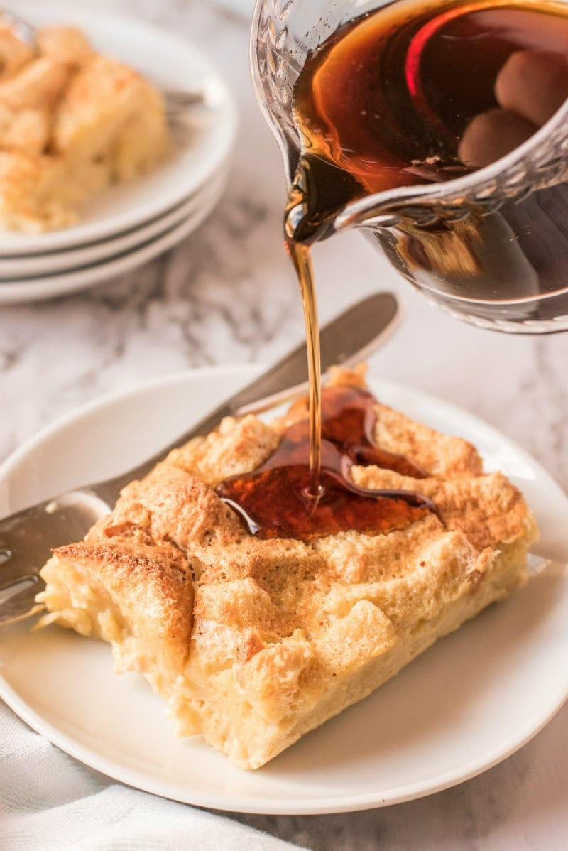 syrup poured over slice of maple custard bread pudding