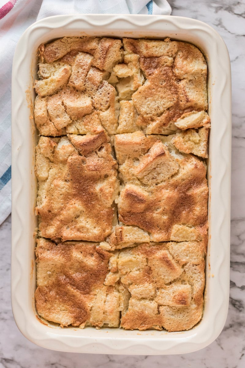 maple custard bread pudding in white casserole dish cut into slices