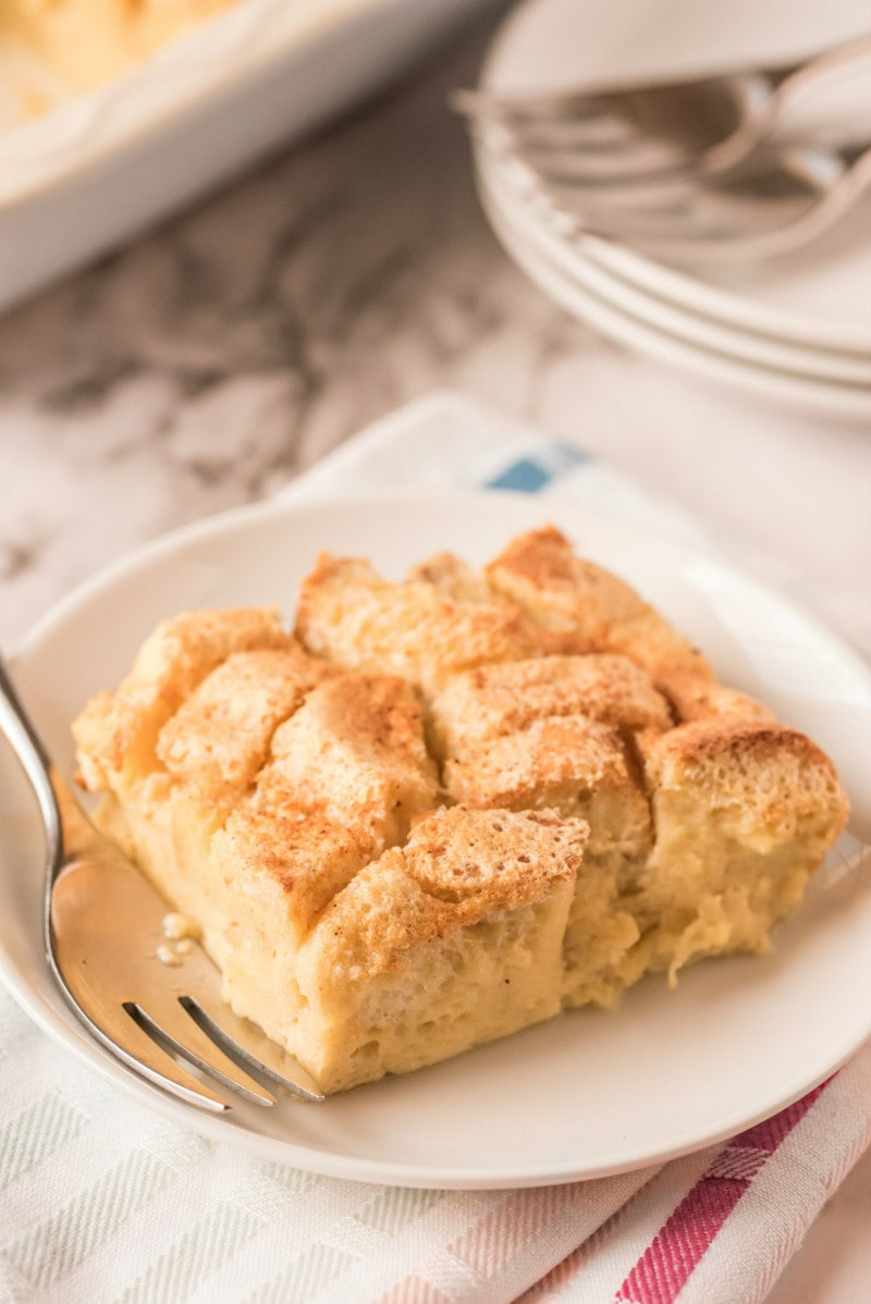 slice of bread pudding on white plate with fork