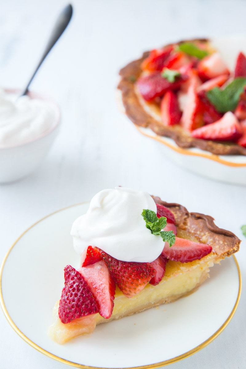 slice of strawberry lemon buttermilk pie on a white plate, garnished with whipped cream. The rest of the pie is in the background