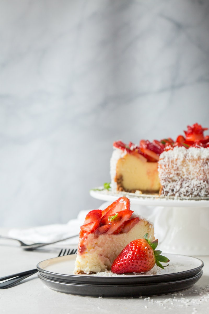 slice of strawberry coconut cheesecake on a white plate with whole cheesecake on display in the background