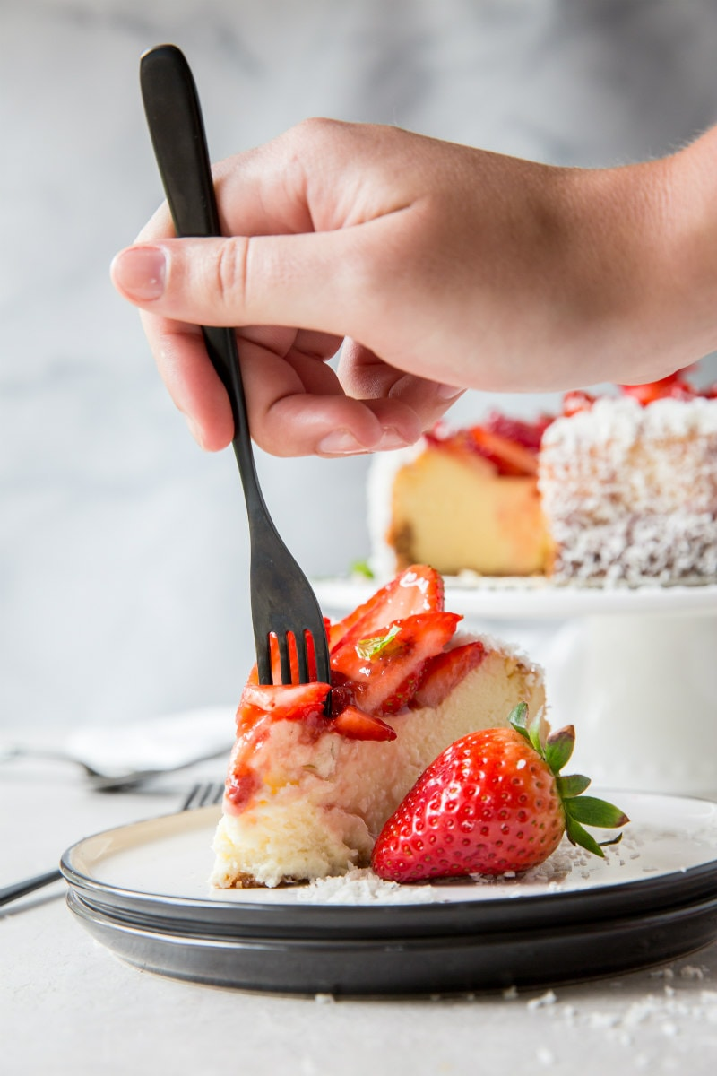 slice of strawberry coconut cheesecake- hand with fork taking a bite