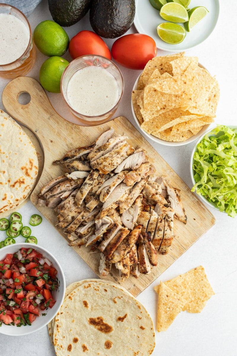 chopped chicken for tacos on wood board surrounded by bowls of taco fixings