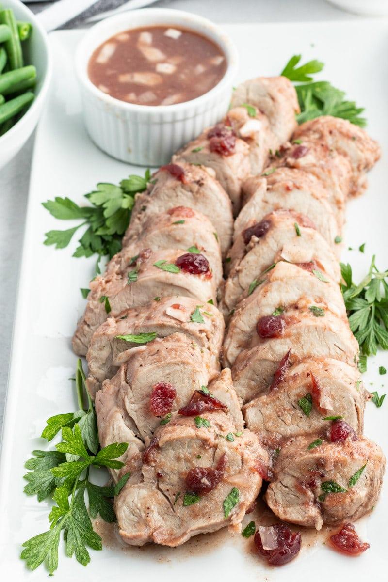 sliced cranberry pork tenderloin on white platter