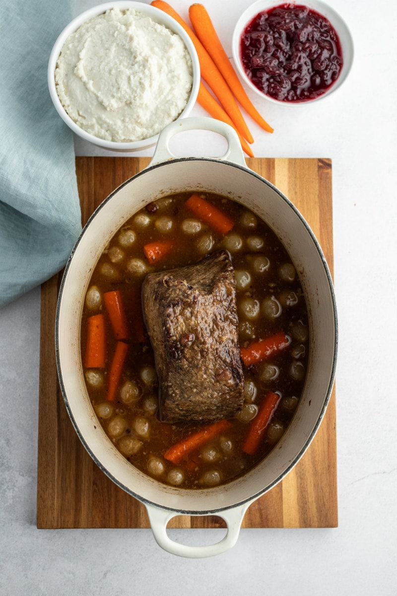 cranberry roast beef in Dutch oven surrounded by carrots and onions