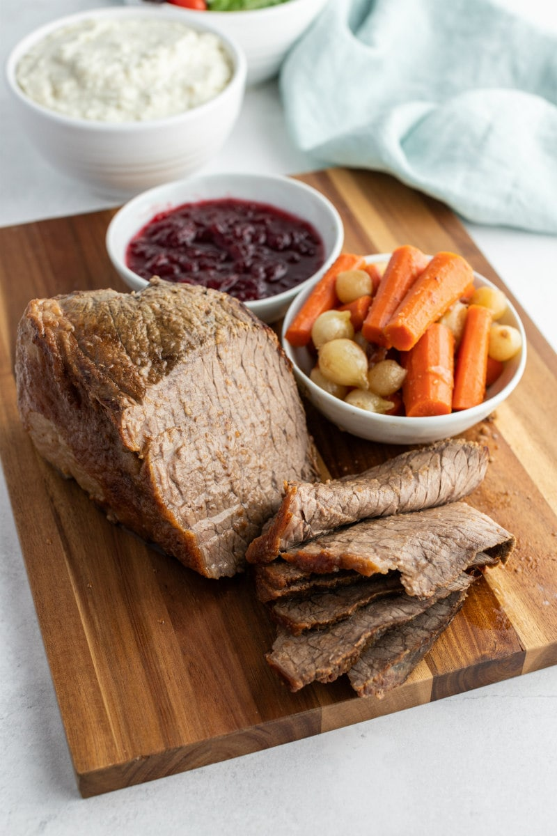 cranberry roast beef sliced on cutting board with vegetables and cranberry sauce