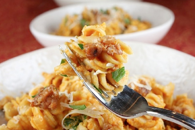 fork of pumpkin pasta over a bowl of it
