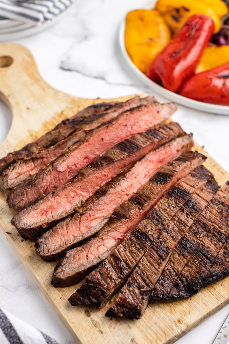 grilled flank steak cut into slices on cutting board
