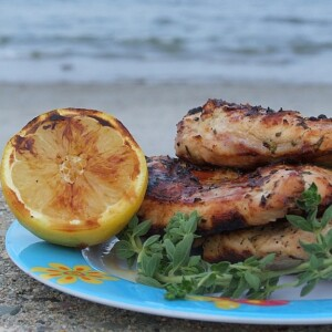 grilled chicken with fresh oregano on a blue plate with a grilled lemon