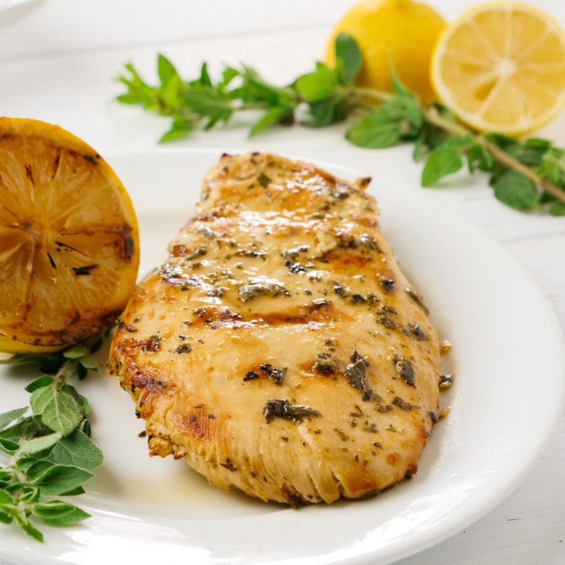 grilled chicken with lemon and oregano on a white plate with a grilled lemon and fresh oregano and fresh cut lemons