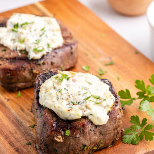 two steaks on a cutting board topped with blue cheese sauce