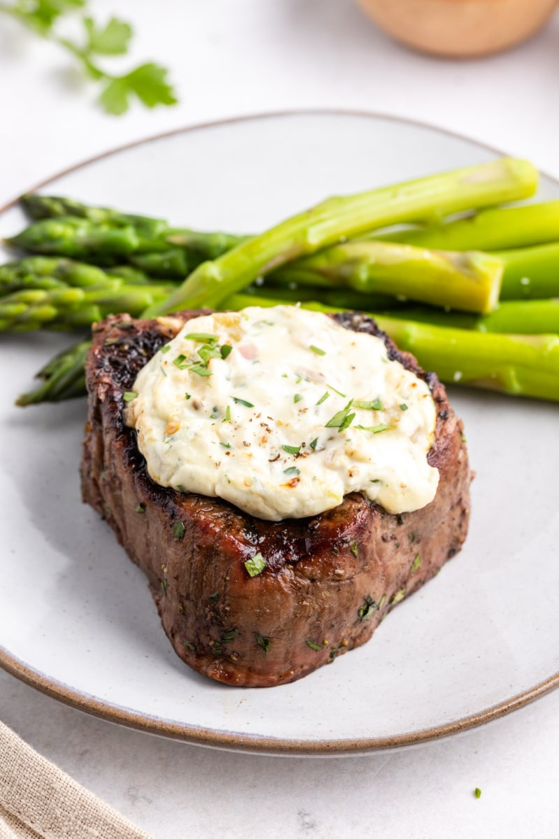 grilled steak with blue cheese and chiles served on white plate with asparagus
