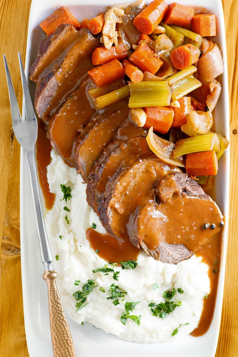 Merlot Pot Roast sliced with sauce and served with vegetables and horseradish mashed potatoes