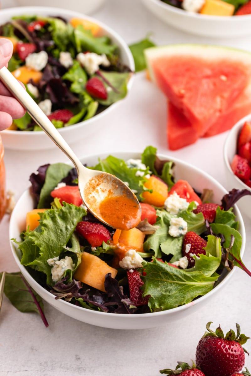 spooning watermelon vinaigrette onto strawberry melon salad