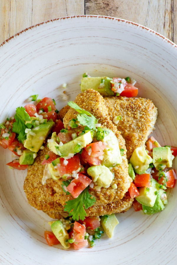 Tequila Almond Chicken on a plate topped with avocado and tomato salad