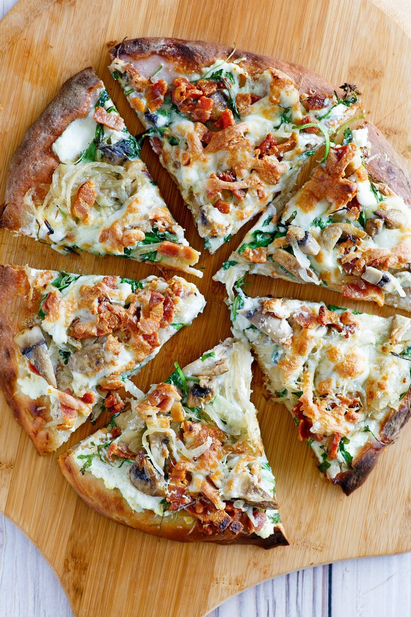 overhead shot of white pizza sliced on a cutting board