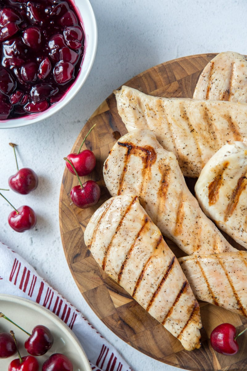 grilled chicken breasts on a wooden board. a bowl of cherry sauce in the background with some fresh cherries scattered around