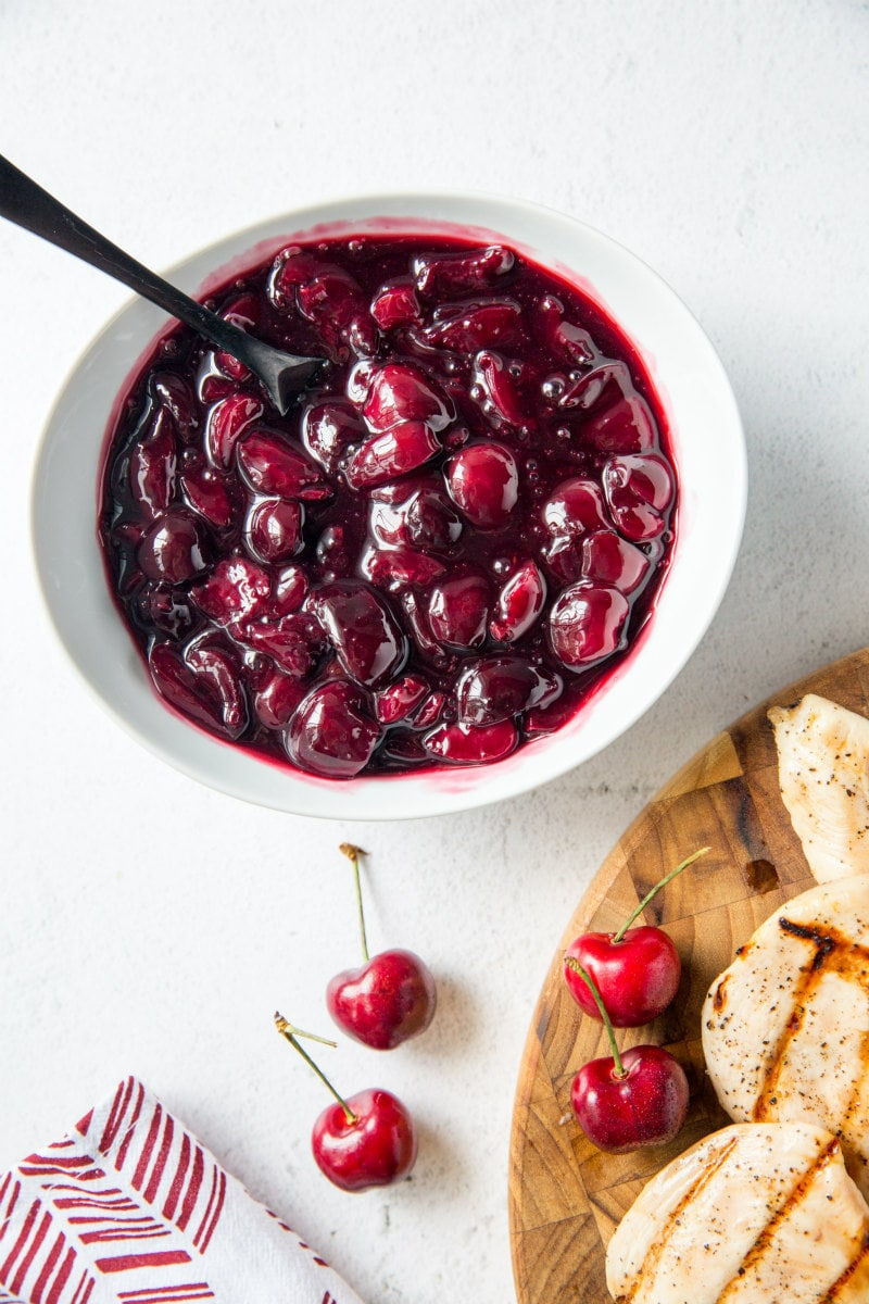 white bowl with fresh cherry sauce and a wooden board with grilled chicken and fresh cherries