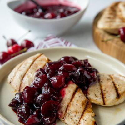 grilled chicken on a white plate with cherry sauce . bowl of cherry sauce in the background