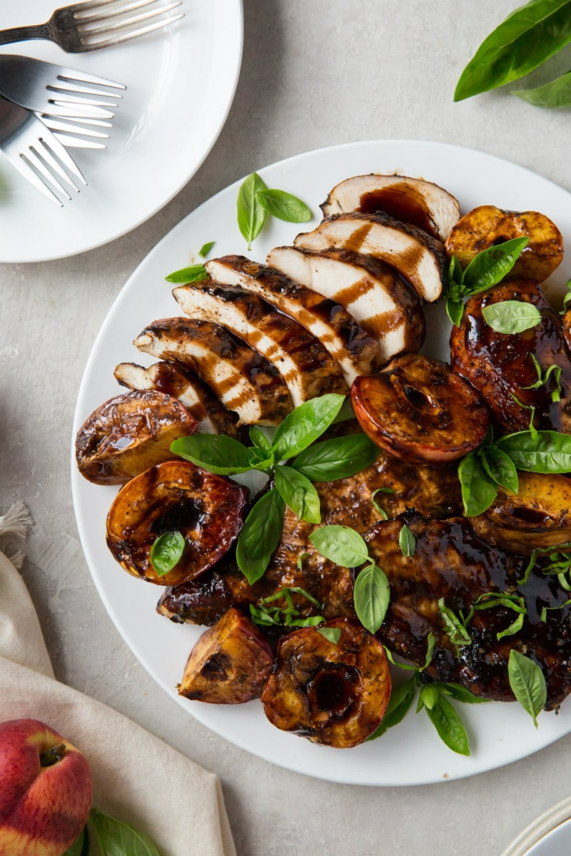 grilled chicken and peaches on a white plate with a plate of forks on the side and garnished with basil