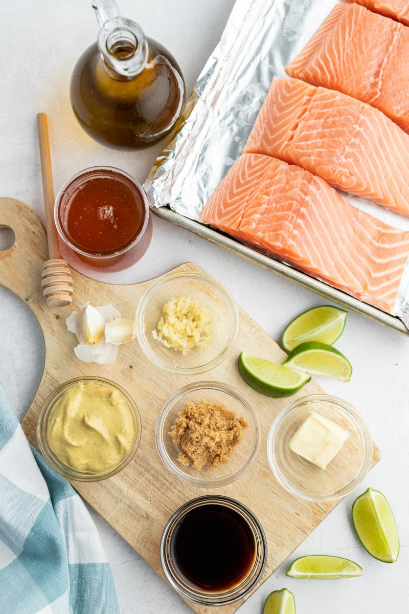 overhead shot of ingredients needed to make barbecued salmon. Ingredients displayed in little glass bowls and cut salmon filets.