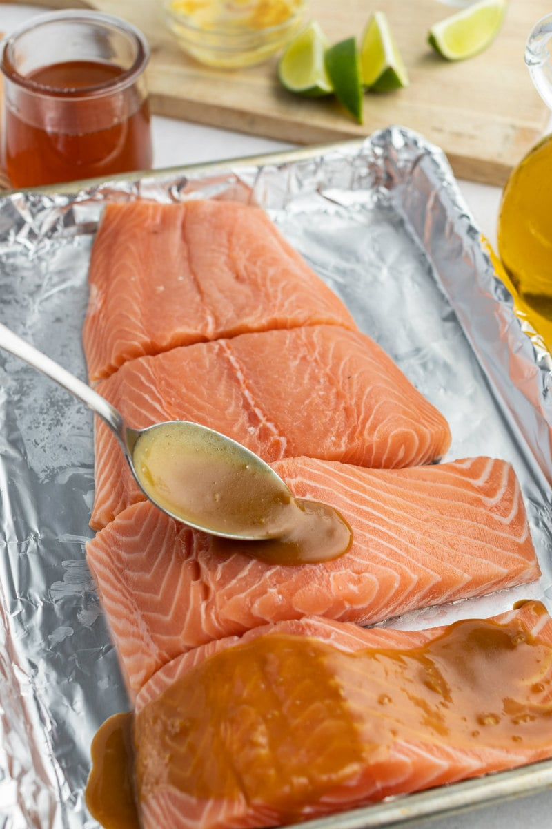 spooning marinade onto salmon filets on a foil lined baking sheet