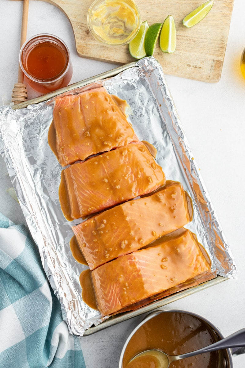 overhead shot of marinated salmon ready for the oven with honey, sauce lime on the side