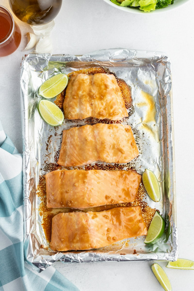 overhead shot of barbecued salmon cooked on a foil lined sheet pan with lime wedges