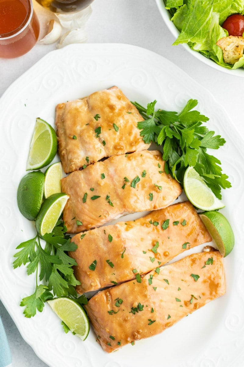 barbecued salmon cut into fillets and displayed on a white plate with parsley and lime wedges