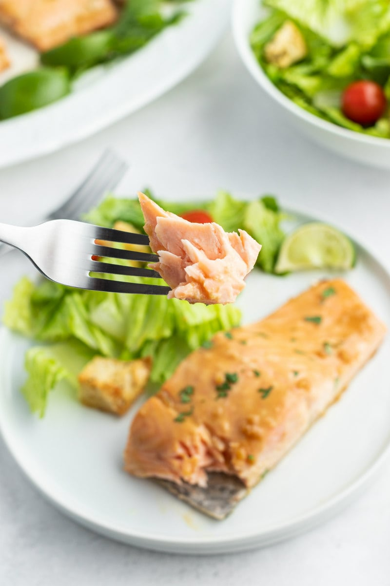 forkful of cooked salmon hovering over a white dinner plate of salmon and salad