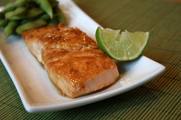 fillet of barbecued salmon on a white serving plate with a lime wedge